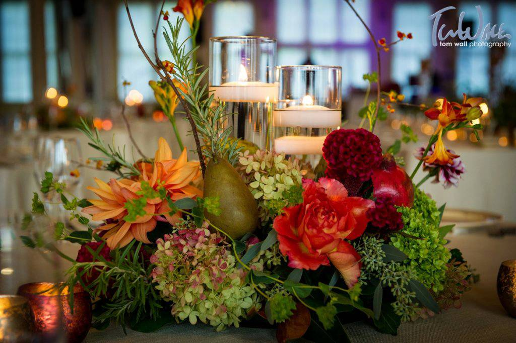 Fall-themed centerpiece, incorporating flowers, fruit and candles, by Surroundings Floral Studio.